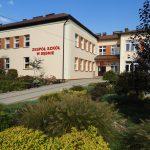 Budynek zespołu szkół w Dębnie widziany od wejścia głównego, przed budynkiem rabaty z krzewami.