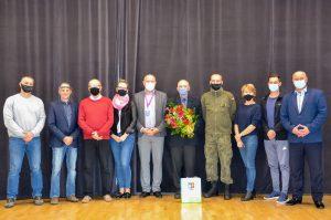 Uczestnicy zjazdu delegatów pozują do zdjęcia na tle brązowej kotary, która znajduje się w auli ZSL.