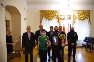 Członkowie zarządu powiatu wraz z przedstawicielami powiatowego zrzeszenia zespołów sportowych i zawodnikami jednej ze zwycięskich drużyn.