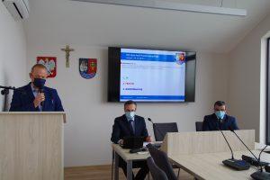 Zdjęcie przedstawia sekretarza powiatu referującego jeden z punktów sesji. Obok, pod ekranem siedzą dwaj członkowie prezydium rady powiatu