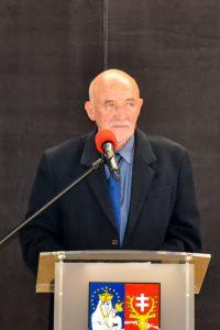 Zdjęcie przedstawia Eugeniusza Jossego stojącego przy mównicy.
