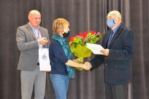 Na zdjęciu Eugeniusz Josse otrzymuje kwiaty i podziękowania od uczestniczki zjazdu oraz dyrektora ZSL Zbigniewa Trębacza. Wydarzeni odbywa się w auli ZSL.