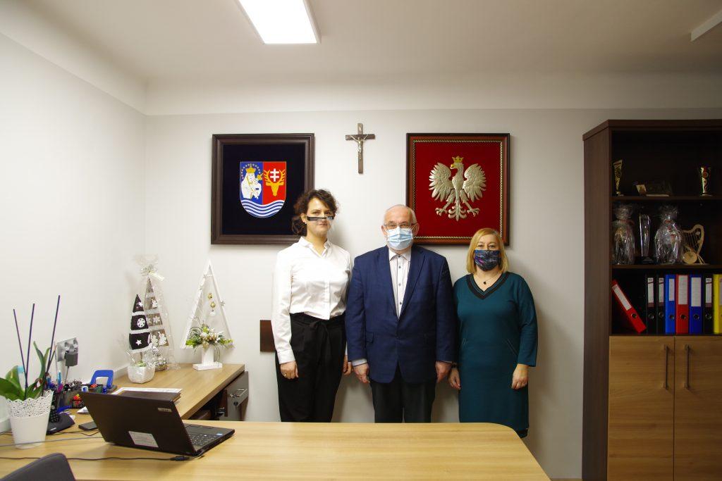 Nauczycielka, starosta oraz naczelniczka wydziału edukacji pozują do zdjęcia na tle szarej ściany. Na niej zawieszone jest godło Polski oraz herb powiatu.