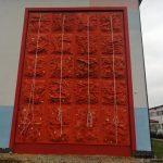 Cała ściana wspinaczkowa ujęta w kadrze. Ściana w kolorze pomarańczowym na tle biało-niebieskiego muru szkoły.