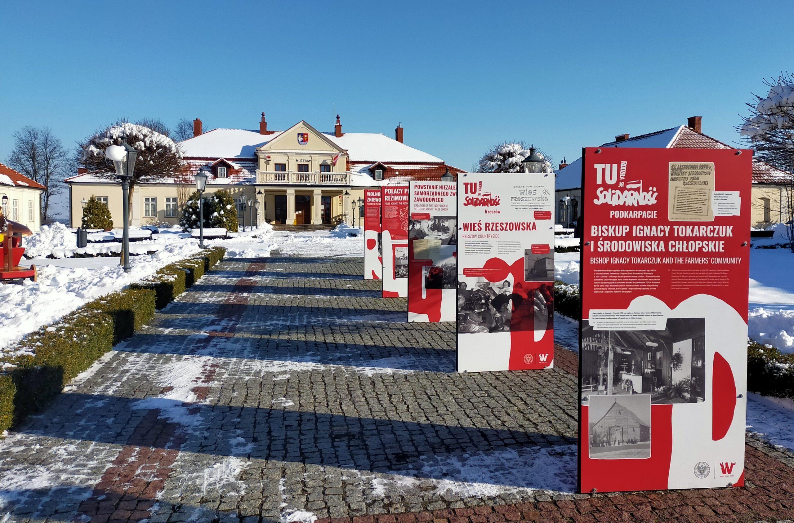 Czerwone plansze z białymi napisami oraz czarno-białymi zdjęciami przedstawiające chronologicznie wydarzenia związane z tematyką wystawy. Plansze ustawione są wzdłuż chodnika prowadzącego do głuwnego wejścia muzeum od strony ulicy Mickiewicza. W tle budynek muzeum.