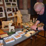 Mężczyzna pokazuje chłopcu dłuta rzeźbiarskie, które zostaną wykorzystane na zajęciach rzemieślniczych z rzeźbienie w drewnie. W tle stoją drewniane figurki postaci i zwierząt oraz sztalugi z planszami, na których znajdują się zdjęcia różnego rodzaju rzeźbionych artefaktów.