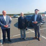 Trzech mężczyzn stojących na parkingu w słoneczny dzień, za nimi w tle stoi granatowe auto