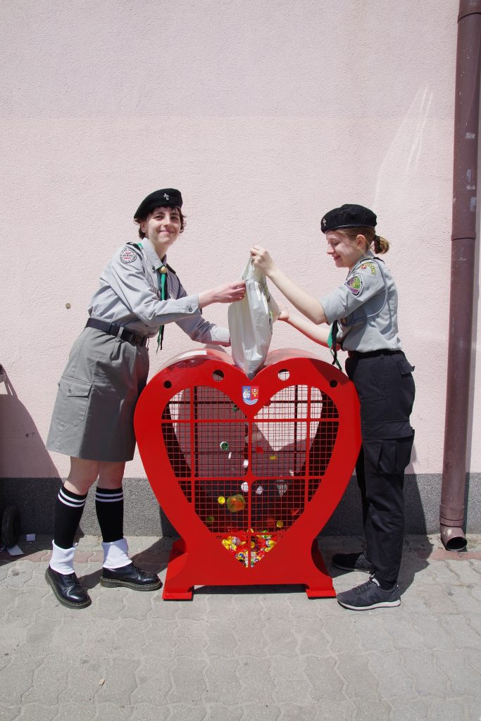 Dwa harcerki wsypują nakrętki do czerwonego pojemnika w kształcie serca.