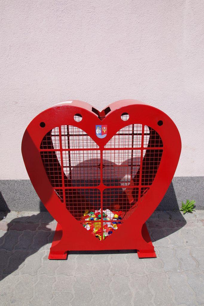 Czerwony metalowy pojemnik w kształcie serca, z siatką z przodu i z tyłu, ustawiony na tle beżowej ściany. W środku niewielka ilości nakrętek.