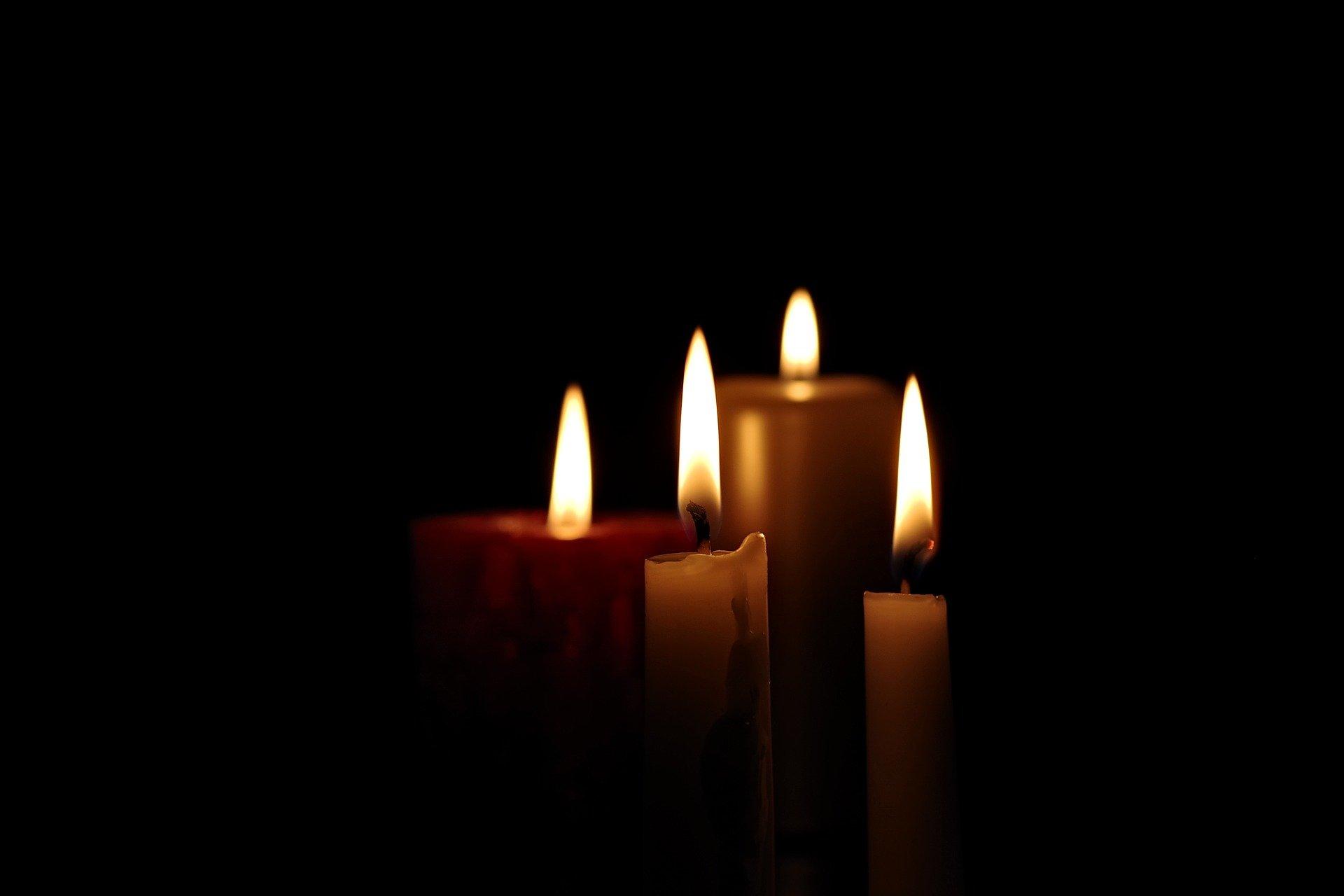 Cztery palące się w ciemności świece o różnej grubości i wielkości