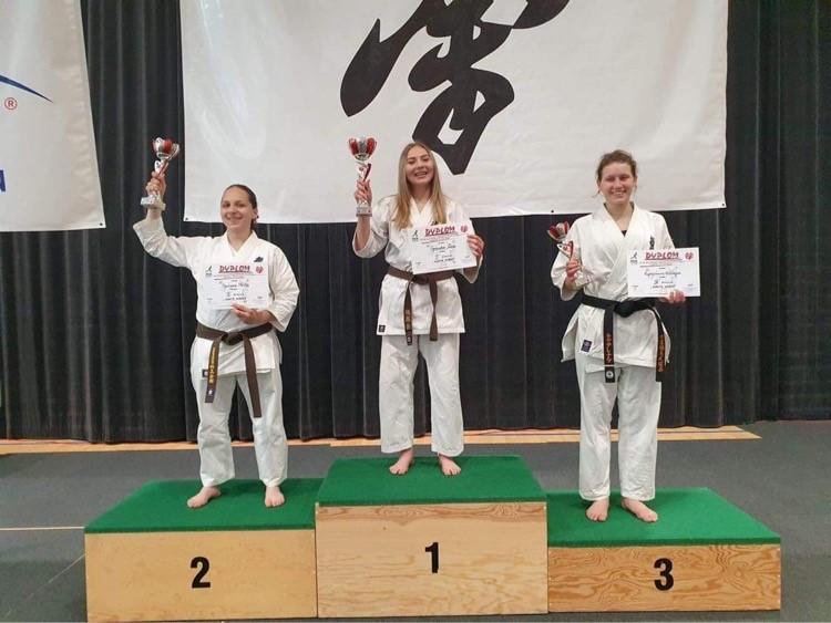 Trzy kobiety stojące na podium ubrana w białe stroje do karate.