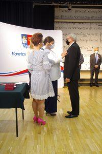 Dwie kobiety oraz mężczyzna. Jedna z kobiet przypina medal do piersi mężczyzny.