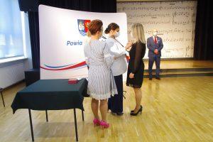 Trzy kobiety. Jedna z kobiet przypina medal do piersi kobiety w czarnej sukience.