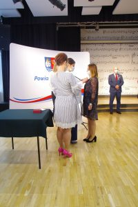 Trzy kobiety. Jedna z kobiet przypina medal do piersi kobiety w sukience w kwiaty.