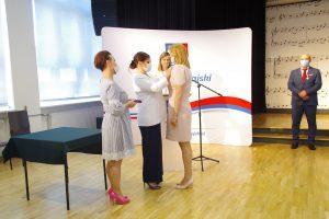 Trzy kobiety. Jedna z kobiet przypina medal do piersi kobiety w sukience w kolorze bladoróżowym.