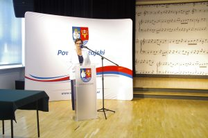 Kobieta w białej marynarce i granatowych spodniach stoi przy mównicy i przemawia. W tle biały baner z herbem powiatu leżajskiego