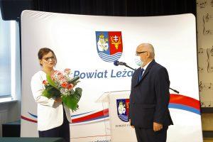 Kobieta w białej marynarce i granatowych spodniach oraz mężczyzna w ciemnoszarym garniturze stoją na tle białego baneru z herbem powiatu i napisem Powiat Leżajski. Kobieta trzyma bukiet kwiatów.