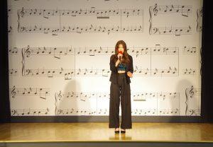 Kobieta w czarnych spodniach i czarnej bluzce stoi na scenie i śpiewa. W tle ściana ozdobiona rysunkami pięciolinii i nut.