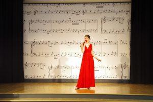 Kobieta w długiej czerwonej sukni stoi na scenie i śpiewa. W tle ściana ozdobiona rysunkami pięciolinii i nut.