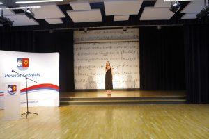 Kobieta w czarnej sukience stoi na scenie i śpiewa. W tle ściana ozdobiona rysunkami pięciolinii i nut.