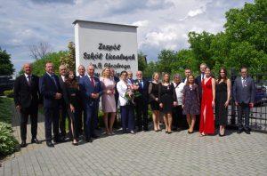 Grupa osób pozuje na tle jasnej ściany. Na ścianie napis Zespół Szkół Licealnych im. Bolesława Chrobrego w Leżajsku