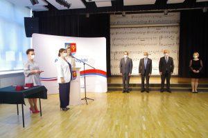 Kobieta ubrana w białą marynarkę i granatowe spodnie stoi przy mównicy i przemawia.