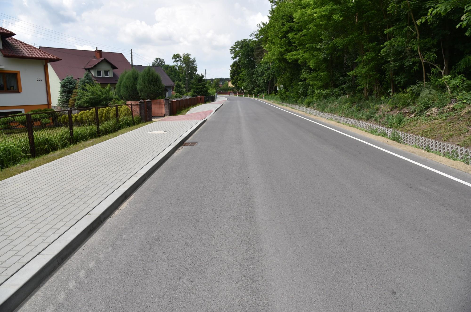Zdjęcie przedstawia drogę po przebudowie z chodnikiem lewostronnym. Po prawej stronie fragment lasu, po lewej zabudowania z z przydomowymi ogródkami