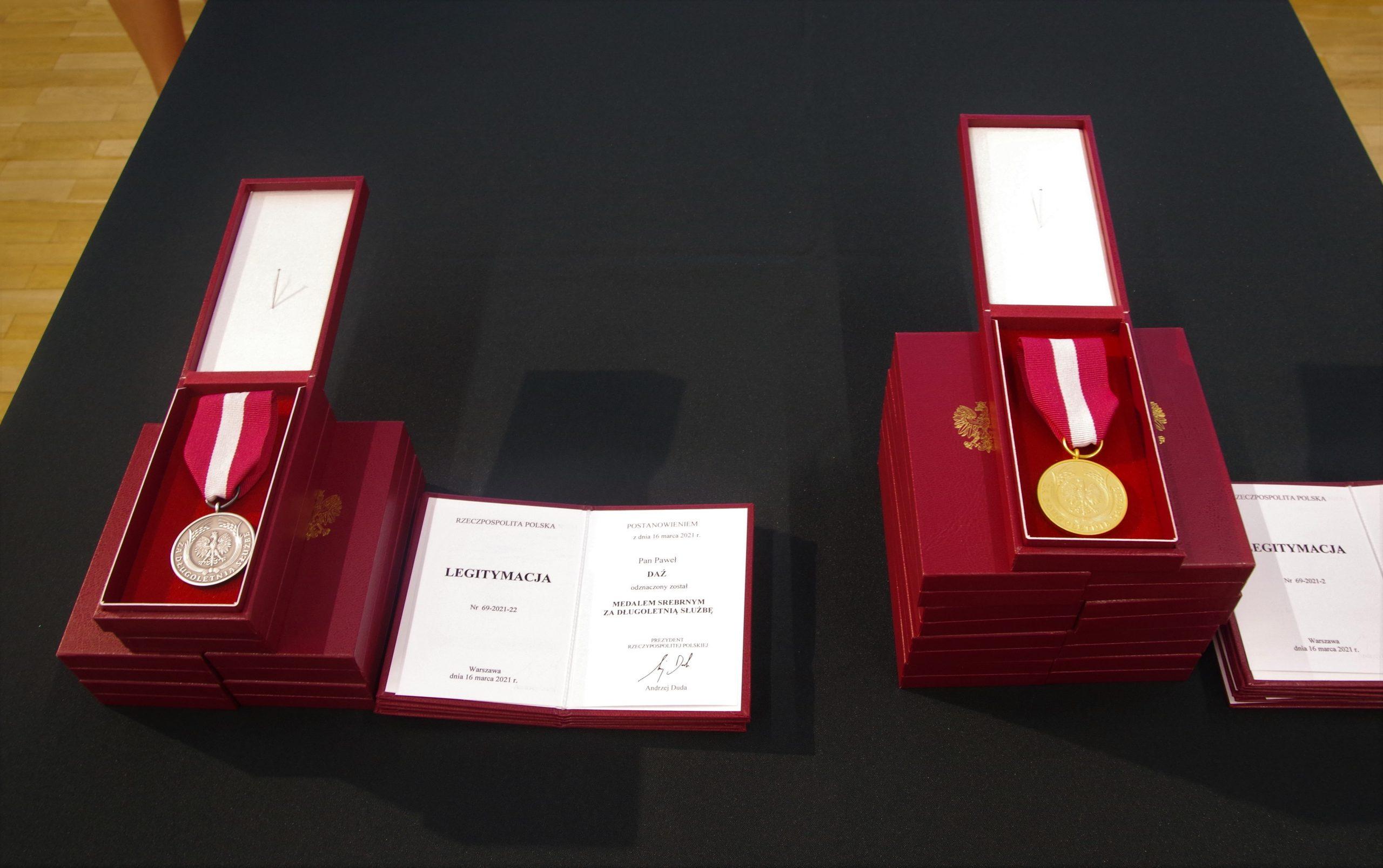 Dwa medale złoty i srebrny w bordowych pudełkach leżące na stole przykrytym ciemnozieloną tkaniną