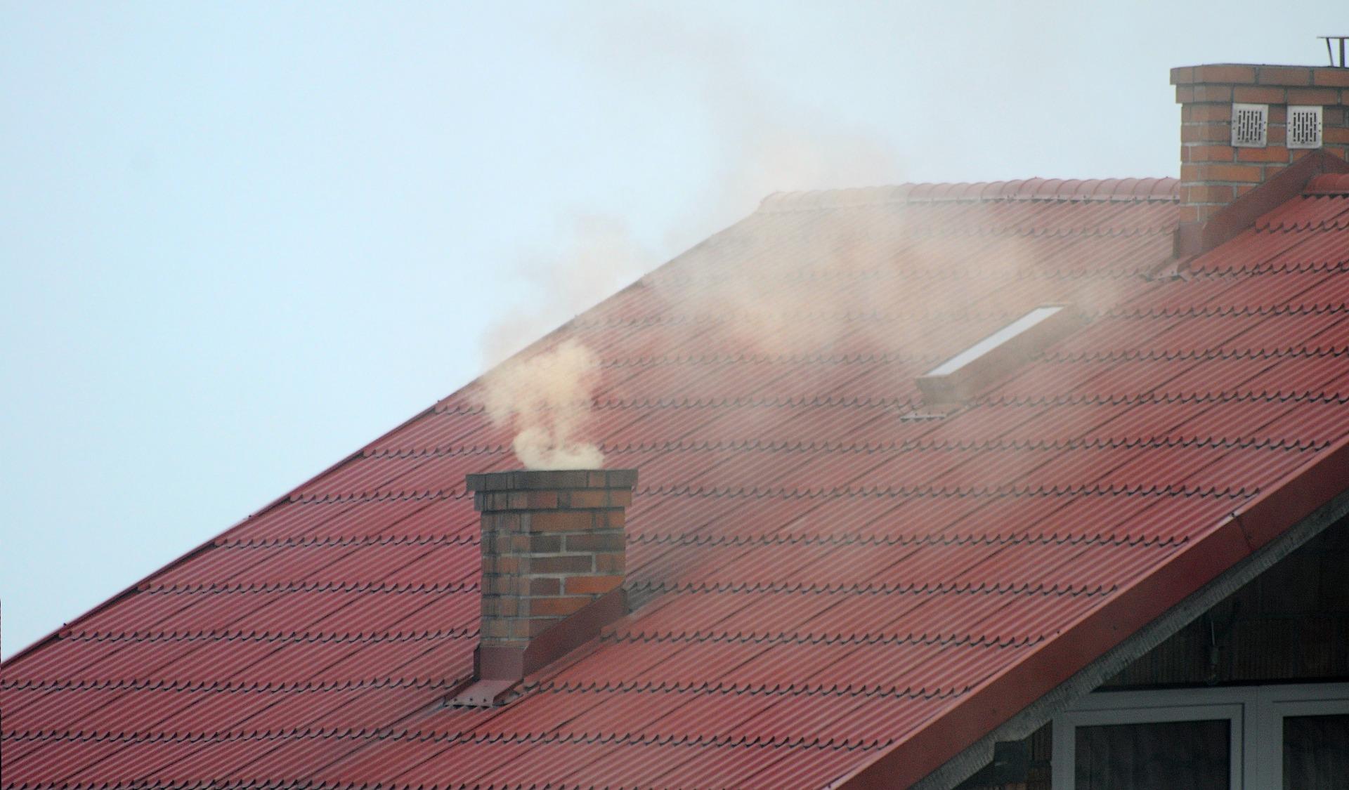 Fragment czerwonego dachu domu jednorodzinnego z widocznym na nim kominem, z którego unosi się gęsty dym.