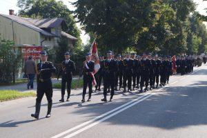 Kompania honorowa Państwowej Straży Pożarnej maszeruje w pochodzie ze sztandarem.