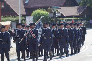 Kompania honorowa Służby Więziennej z Rzeszowa maszeruje w pochodzie. Na przedzie niesiony jest sztandar.
