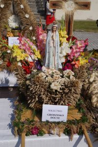 Wieniec dożynkowy wykonany ze zbóż. W jego centralnej części znajduje się gipsowa figurka Matki Boskiej w biało-błękitnych szatach.