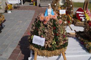 Wieniec dożynkowy wykonany ze zbóż. Kształtem przypomina stożek, na którego szczycie znajduje się gipsowa figurka Matki Boskiej w biało-niebieskich szatach.