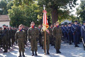 Kompania honorowa oddziału saperów stojąca w szyku na placu przed sanktuarium przodem do ołtarza.. Jeden z żołnierzy trzyma sztandar oddziału.