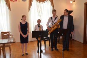 Wnętrze sali konferencyjnej. Dziewczynka, dwóch chłopców i dorosły mężczyzna stoją przed fortepianem. Chłopcy trzymają saksofony. Przed nimi umieszczono dwa pulpity na stojakach.