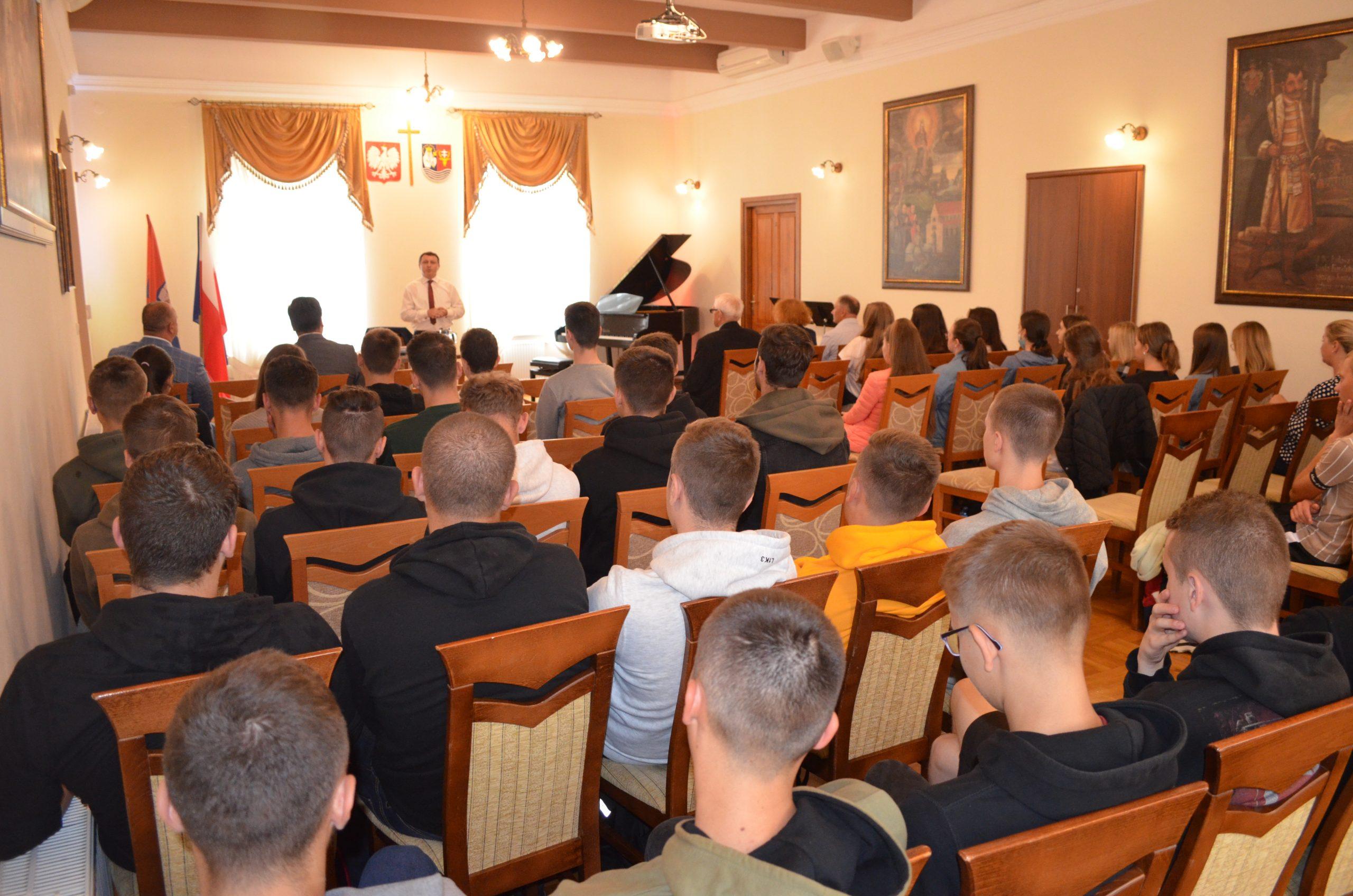 Uczniowie szkół średnich siedzą na sali konferencyjnej muzeum, widok z końca sali, w tle osoba przemawiająca, w sali panuje żółte światło.