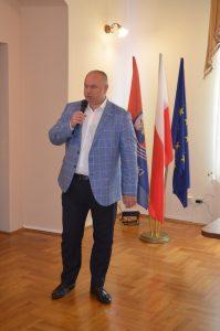 Wnętrze sali konferencyjnej, na środku stoi przemawiający mężczyzna, ma niebieską marynarkę, a w tle umieszczono stojak z flagami Powiatu Leżajskiego, Polski i Unii Europejskiej.