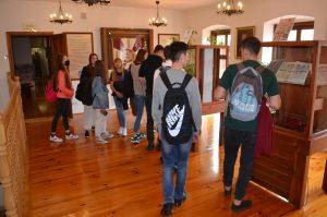 Wnętrze sali wystawowej. Na pierwszym planie dwóch uczniów zwiedzających wystawę odwróconych do obiektywu tyłem. W tle grupka innych uczniów.