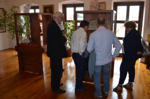 Wnętrze sali wystawowej. Trzech mężczyzn stoi przed gablotą i ogląda umieszczone w niej artefakty. Stoją tyłem i bokiem do obiektywu.