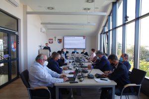 Sala obrad rady powiatu, na środku stół przy którym po obu stronach siedzą mężczyźni oraz kobiety. W tle na ścianie wisi ekran.