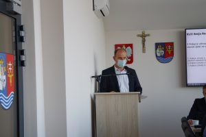 Mężczyzna stoi przy mównicy i przemawia, za nim na białej ścianie wisi godło Polski, krzyż orz herb powiatu leżajskiego, po prawej stronie widać fragment monitora zawieszonego na ścianie, po lewej fragment przeszklonych drzwi wyjściowych.