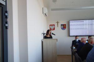 Kobieta stoi przy mównicy, za nią na białej ścianie wisi godło Polski, krzyż oraz herb powiatu Leżajskiego, po prawej widoczny fragment monitora oraz siedzący przy stole mężczyzna.