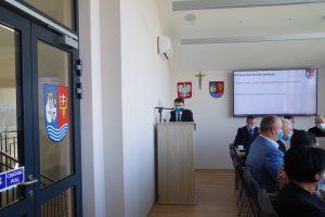 Mężczyzna stoi przy mównicy, na białej ścianie wisi godło Polski, krzyż oraz herb powiatu leżajskiego. Po prawej stronie widoczne plecy siedzących przy stole mężczyzn, po lewej fragment przeszklonych drzwi wyjściowych.
