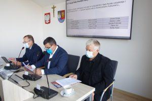 Trzech mężczyzn siedzących za stołem, za nimi znajduje się wiszący na białej ścianie monitor, na którym widnieją wyniki głosowania. Obok niego wiszą: godło Polski, krzyż oraz herb powiatu leżajskiego.
