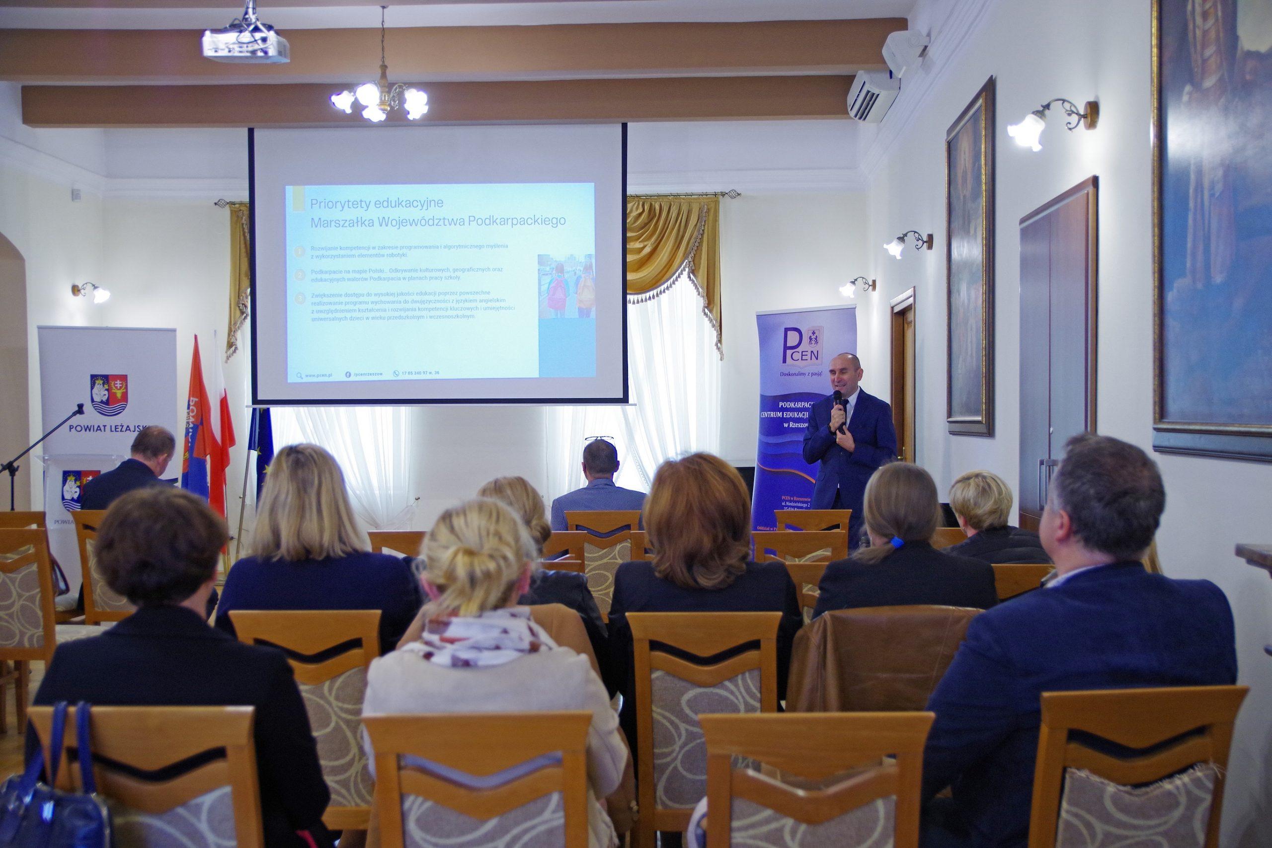 Na pierwszym planie siedzą uczestnicy konferencji zwróceni tyłem do obiektywu, a przodem do przemawiającego mężczyzny. Za mężczyzną wisi ekran projektora, na którym wyświetlana jest prezentacja.